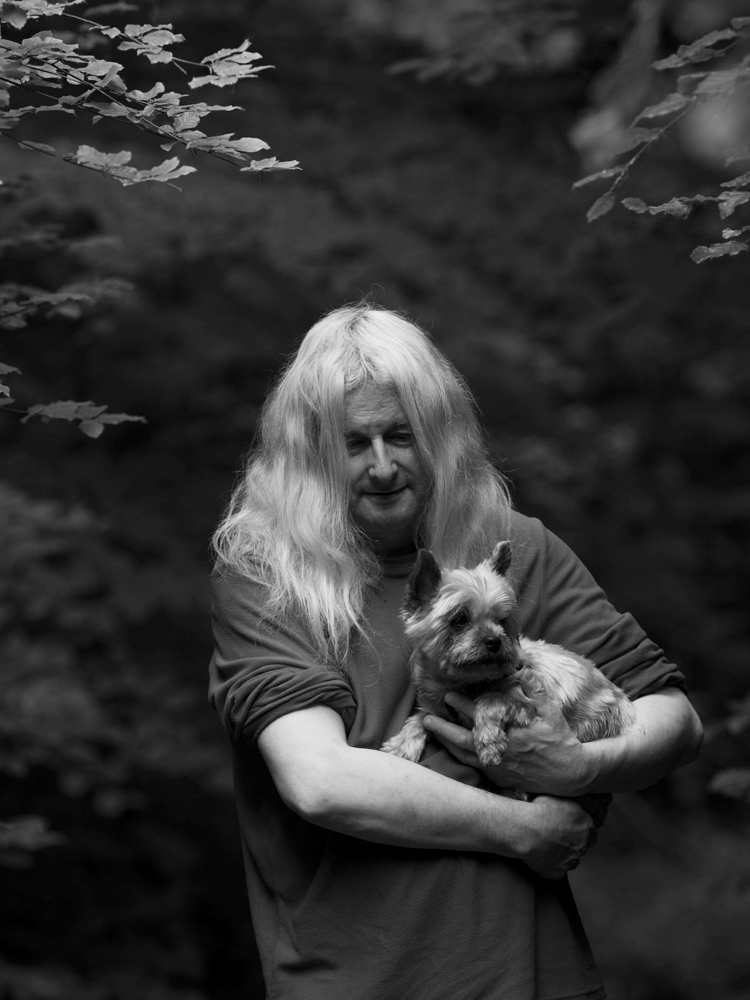 Photography by Mario Popham, for wigan arts festival, photographing nature during lockdown. A black and white photograph of a person in nature, holding a dog.