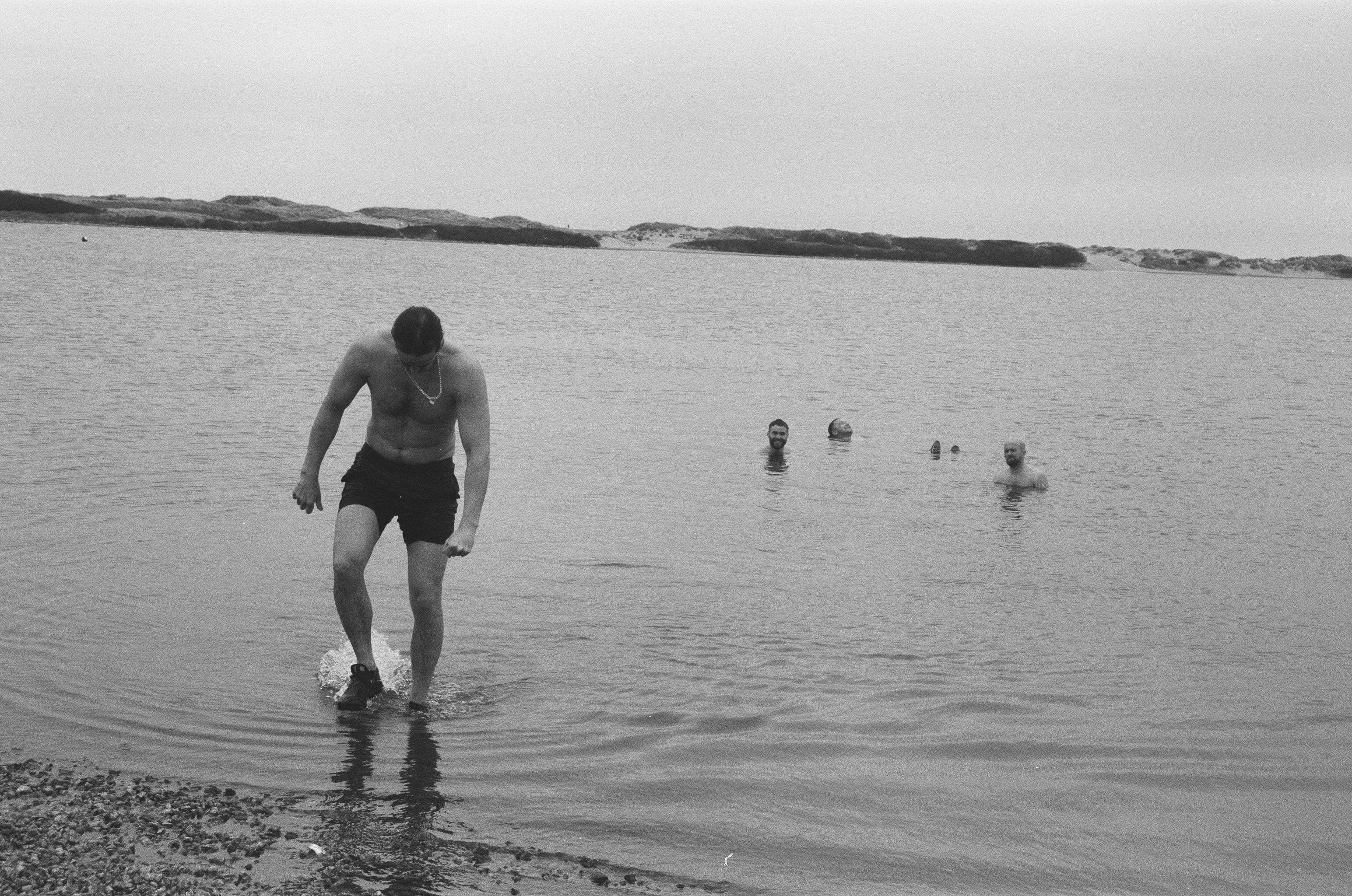 Black and white image of people in group of people swimming - photographs from exhibition from 3 bull mastiffs / one day at a time boys.